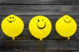 Happiness emotion. Yellow balloon with smile on blue background top view